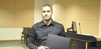 man in black shirt grey pants holding black paper