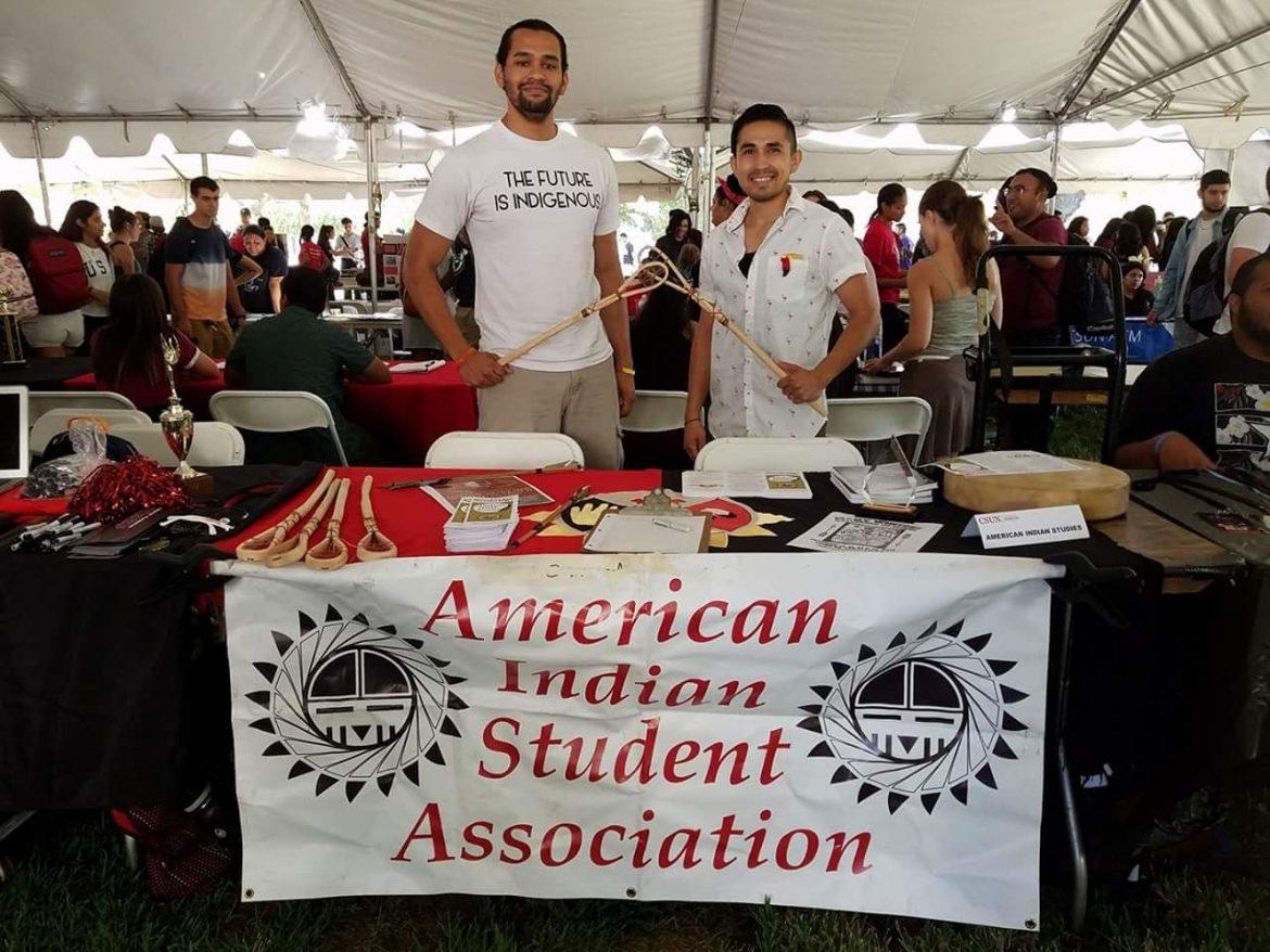 two+male+students+stand+behind+American+Indian+Student+Association+booth