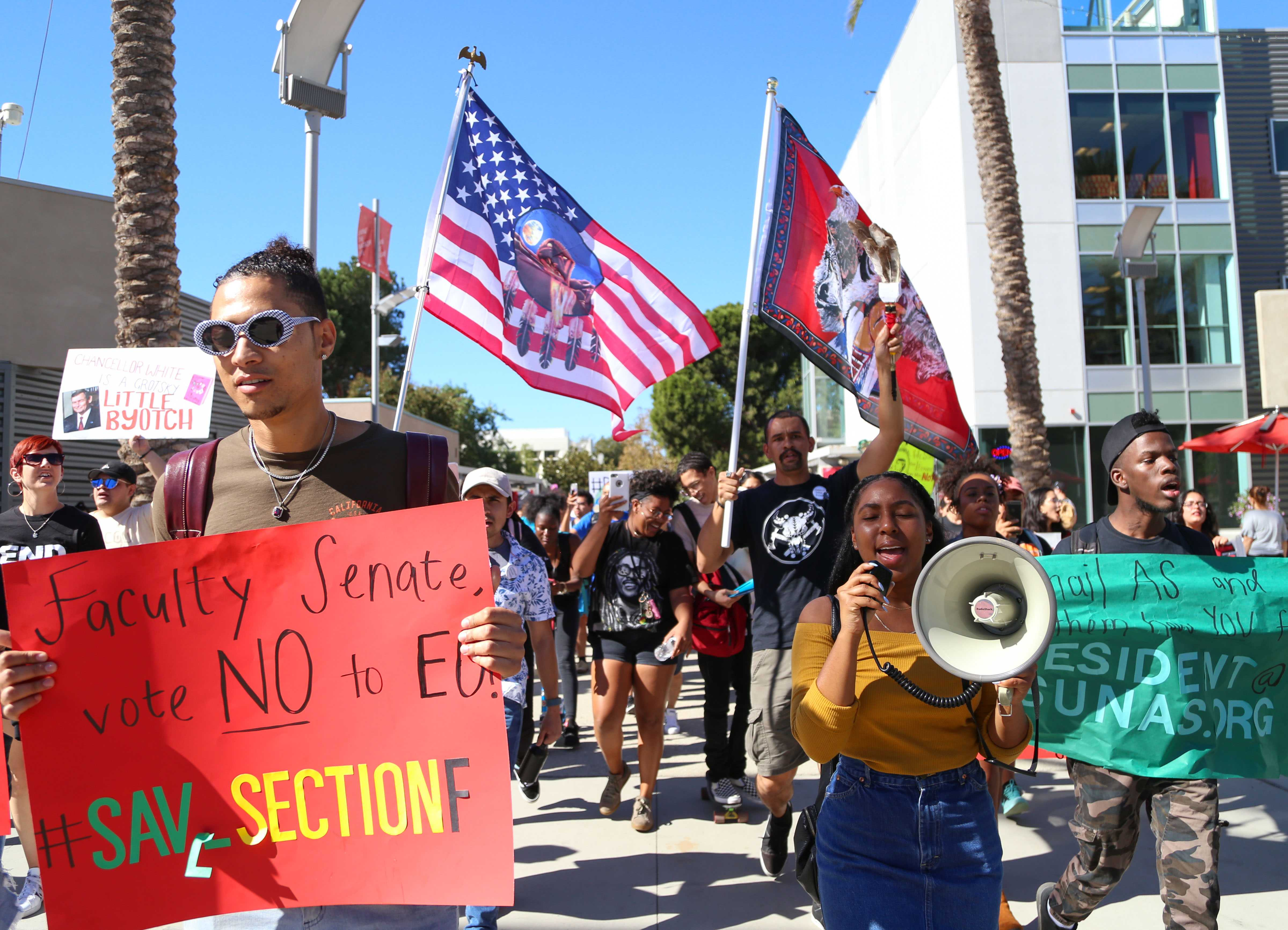CSUN politcal science pre-law major, and Vice President of the Black Student Union, Isaiah Thibodeaux (left) holds up a sign as he marches to protect school Section F from Executive Order 1100 at the University Student Union in Northridge Calif., Wednesday, Oct. 25, 2017. Photo credit: John Hernandez