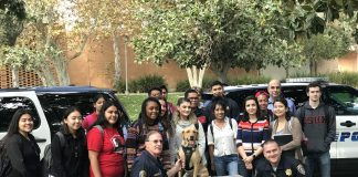 officers dressed in black surrounded by students and brown and lack K9s