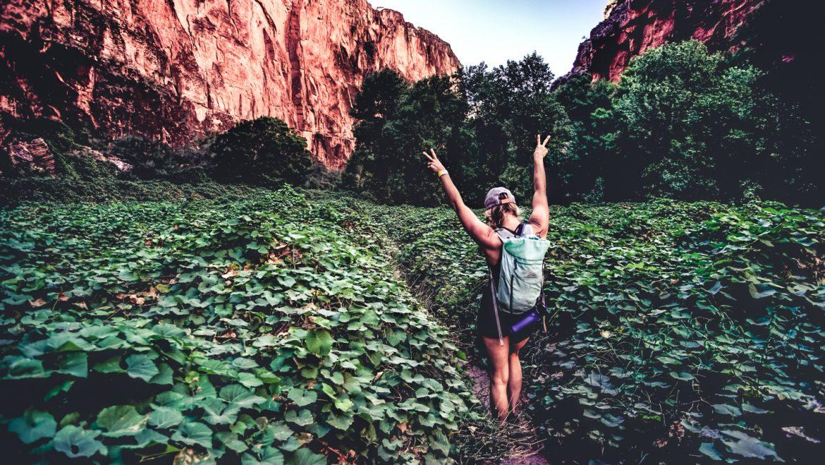 girl posing in green filed surrounded by rust colored rock formations