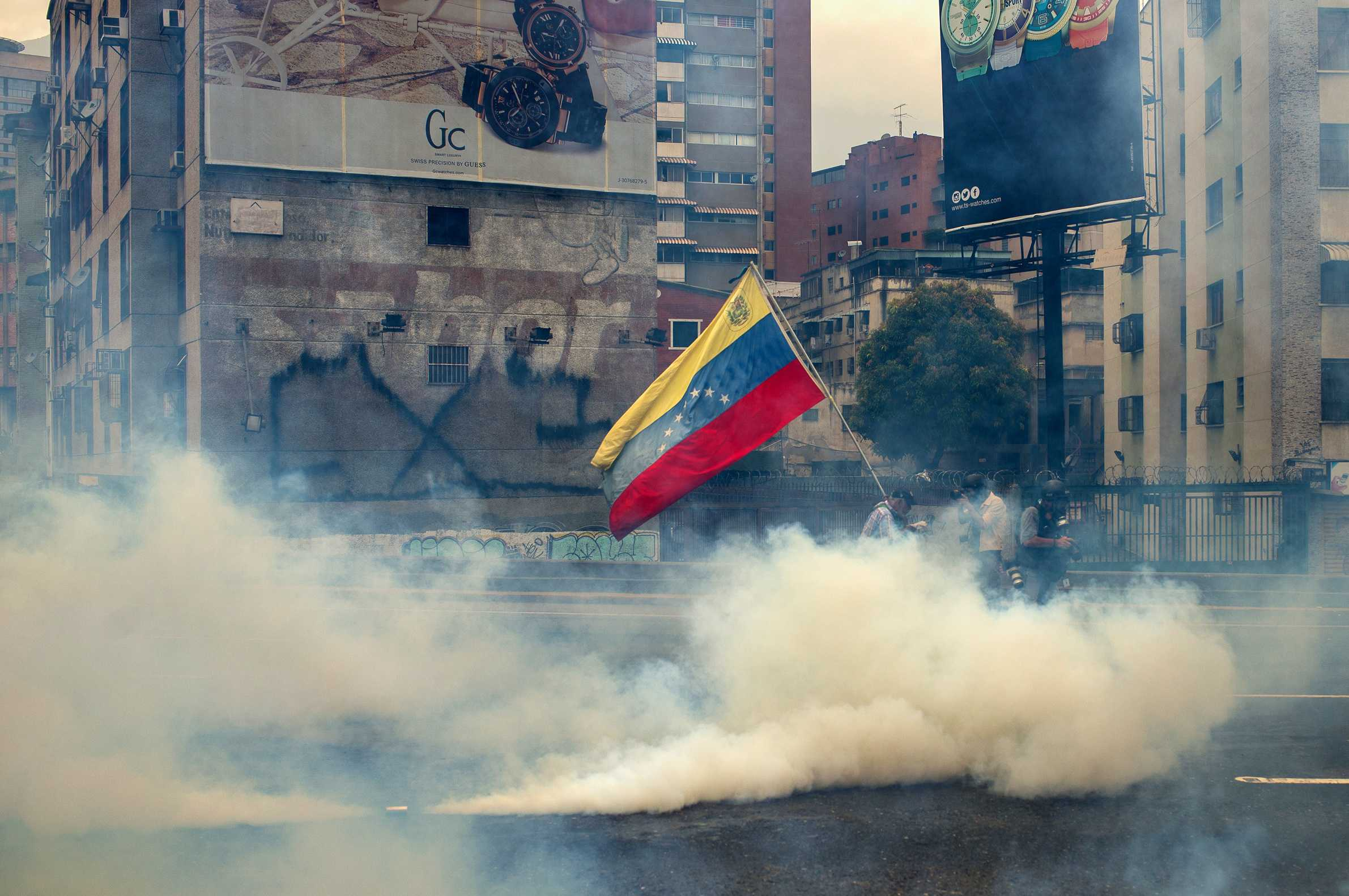 Protesters wearing masks carry the Venezuelan flag amid a tear-gas cloud where mass demonstrations turned into riots in Caracas, Venezuela, on Wednesday, April 19, 2017. The opposition is demanding new elections and holding President Nicolas Maduro responsible for the deep political and economical crisis in the oil-rich country. (Manaure Quintero/DPA/Zuma Press/TNS)