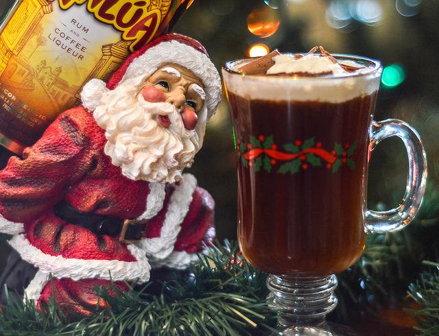 Santa figurine next to cup of rum