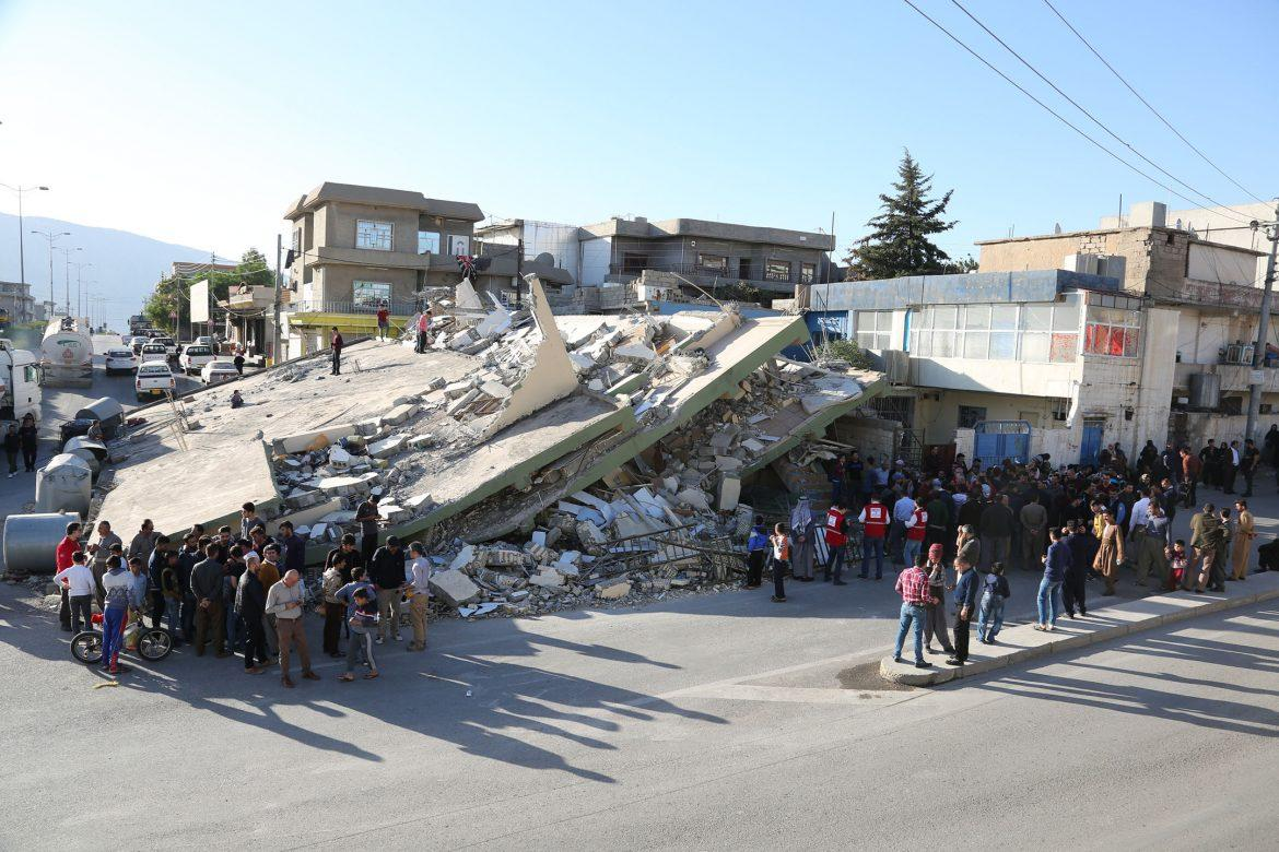 people+stand+around+collapsed+building