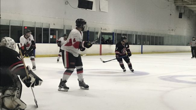 CSUN hockey team in white preparing to score