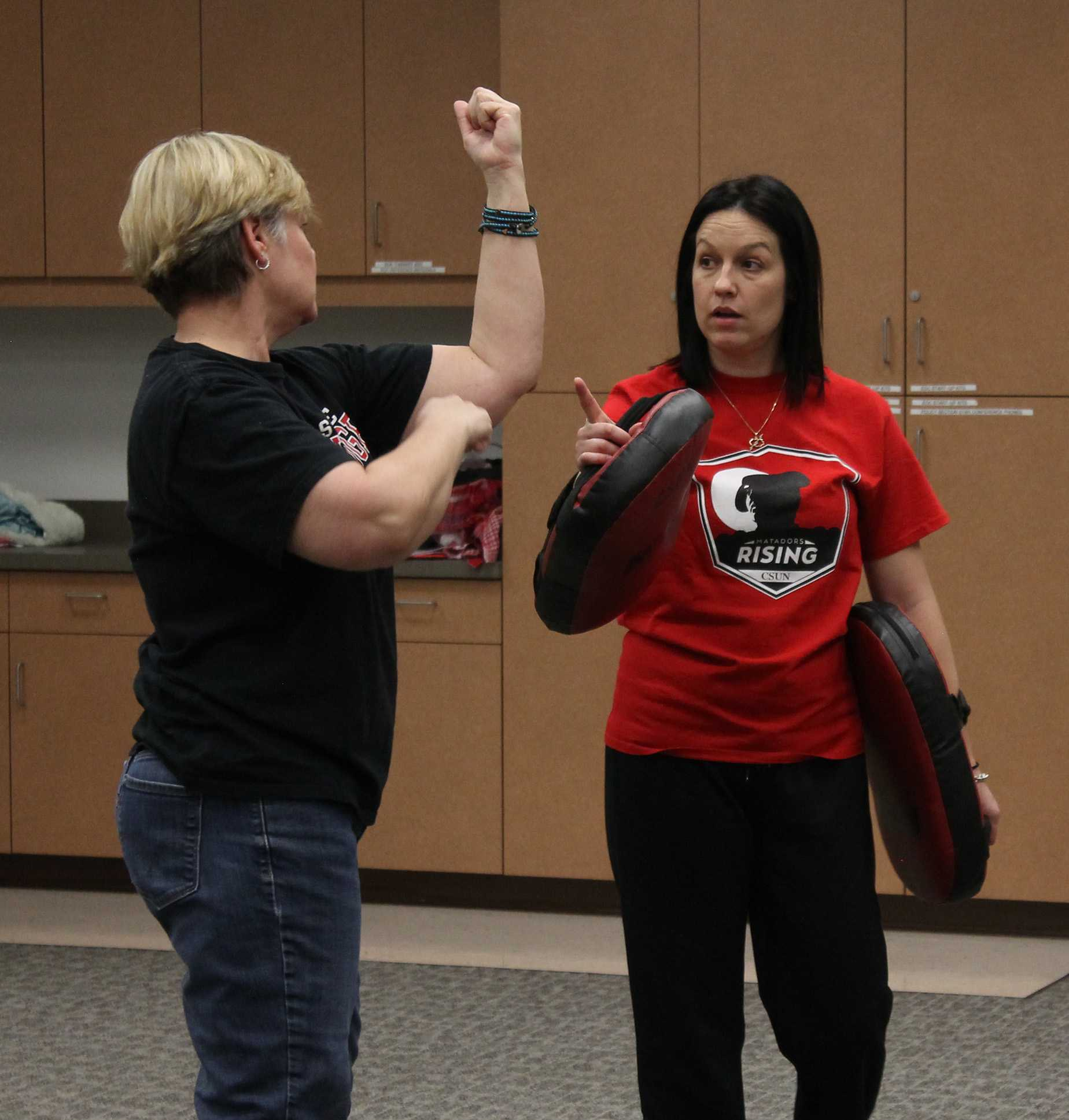 Instructor Stacy Nowak (right) corrects a participant during one of the Tuesday evening classes inside the training room on the 2nd floor of Police Department Services. Photo credit: Clare Calzada