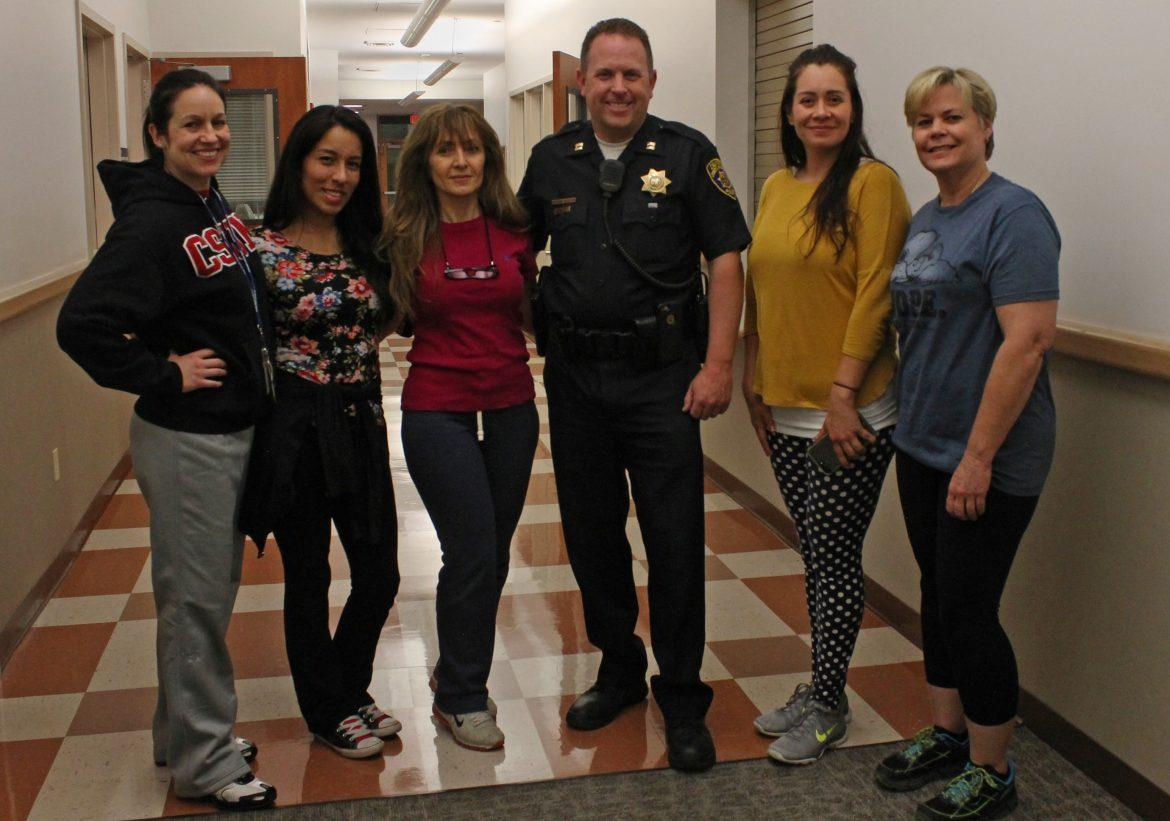 woman pose around police officer in hallway