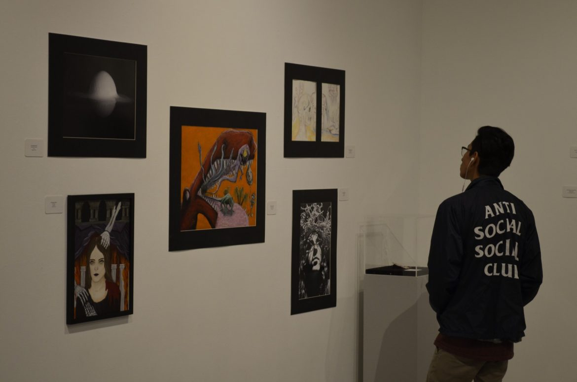 Freshman+Juan+Castillo+admires+work+submitted+by+The+Buckley+School+on+Thursday+afternoon.+Photo+credit%3A+Nick+Rose