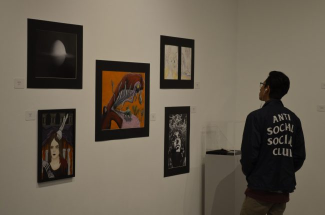 man in black jacket stares at different art works on wall