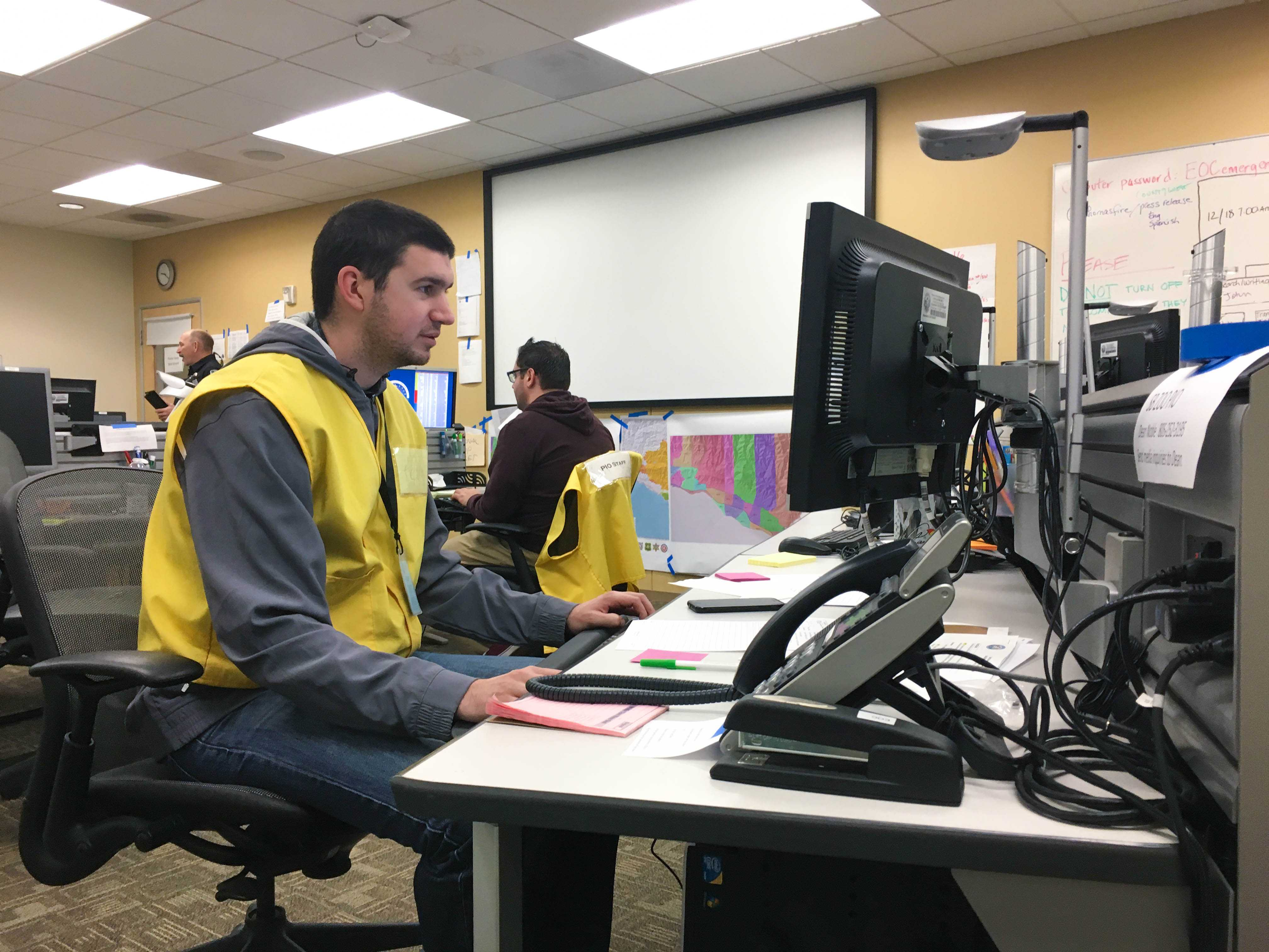 man in yellow vest sits at computer desk