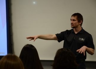 Man in black shirt speaking to students inside of a classroom