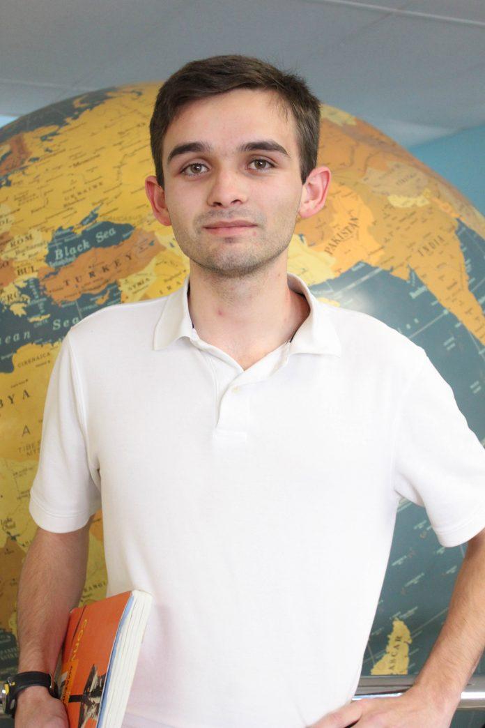 man in white shirt holding orange textbook