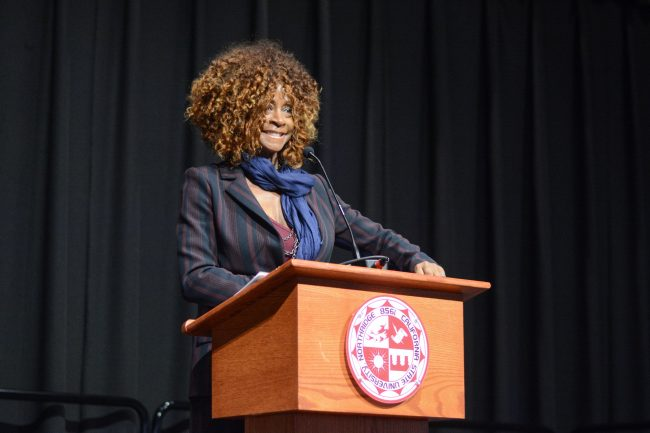 woman dressed in suit happily stands at podium