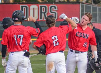 CSUN baseball players in red giving each other a high-five on the field
