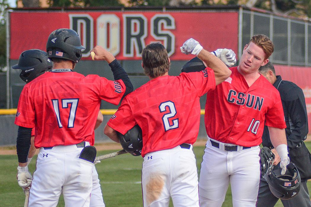 CSUN+baseball+players+in+red+giving+each+other+a+high-five+on+the+field