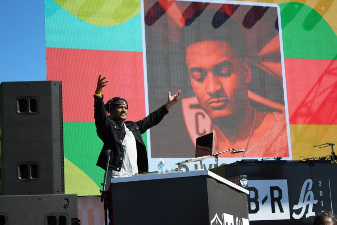 DJ hold his hands up on stage to pump up crowd