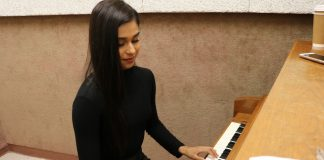 woman dressed in black plays piano