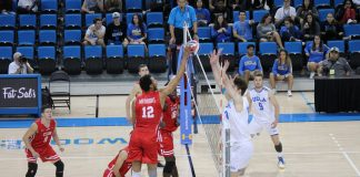 CSUN mens volleyball player goes to tip the ball over the net