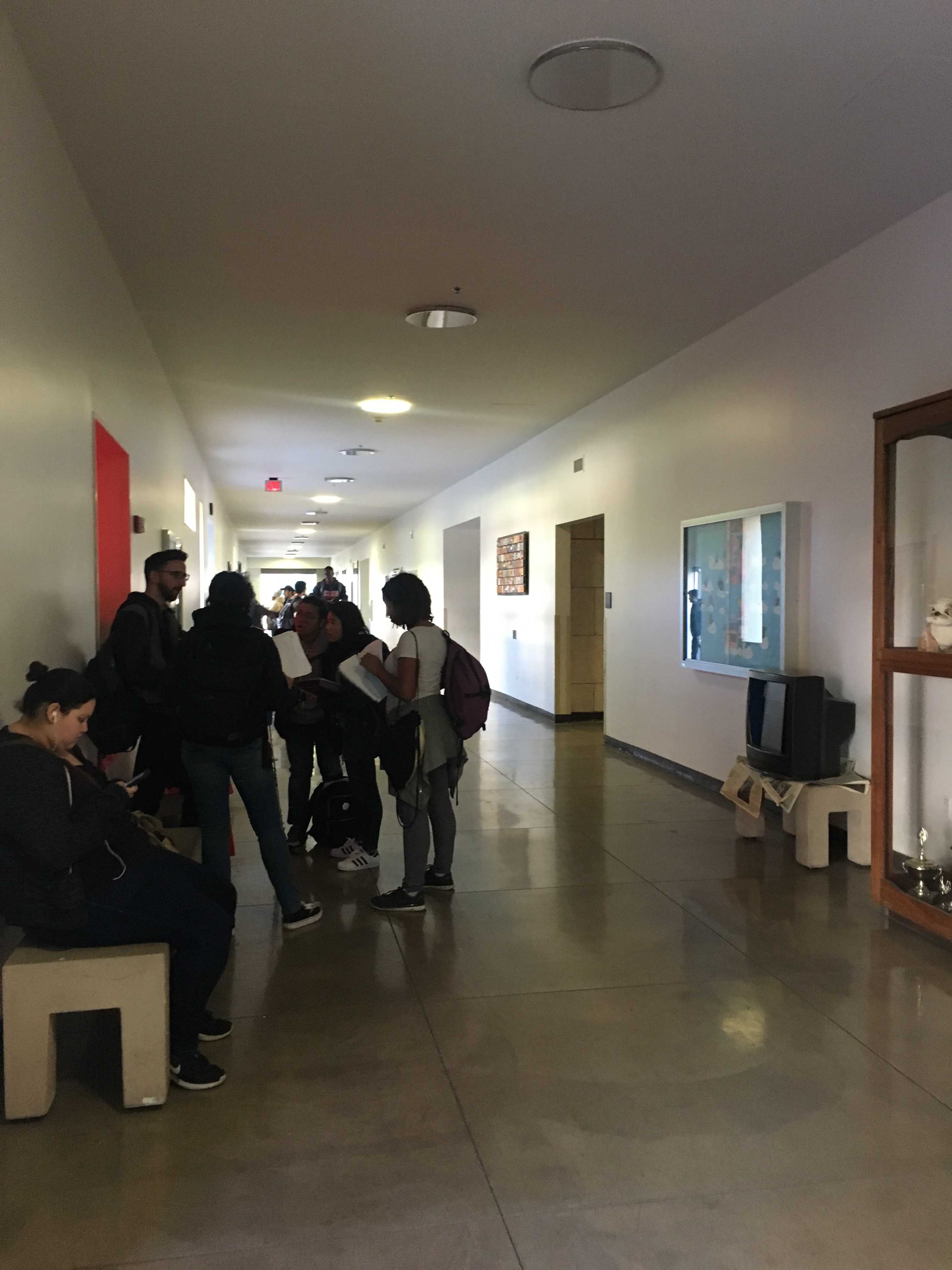 Hallway of Manzanita Hall outside of classroom 130. Students of Physics 220B-Electricity and Magnetism-  wait to hear if their test will be cancelled.