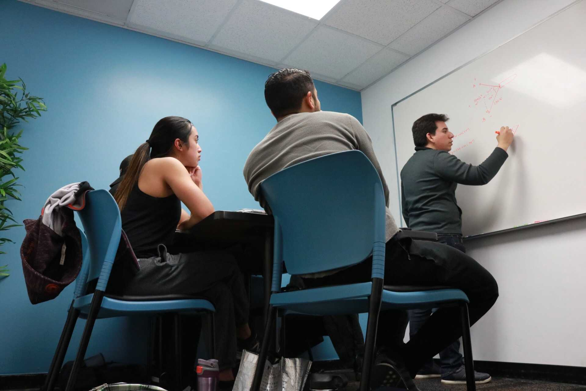 students sit focused while watching a man work on the board