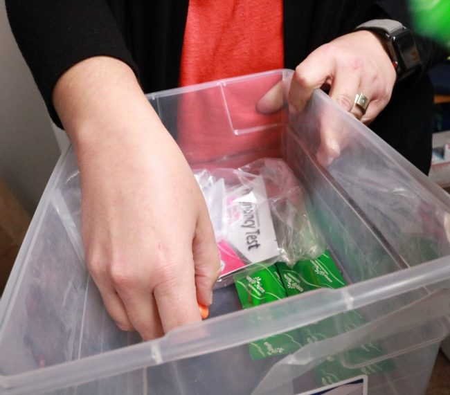 hands holding a plastic bin, inside of it are pregnancy tests and feminine products