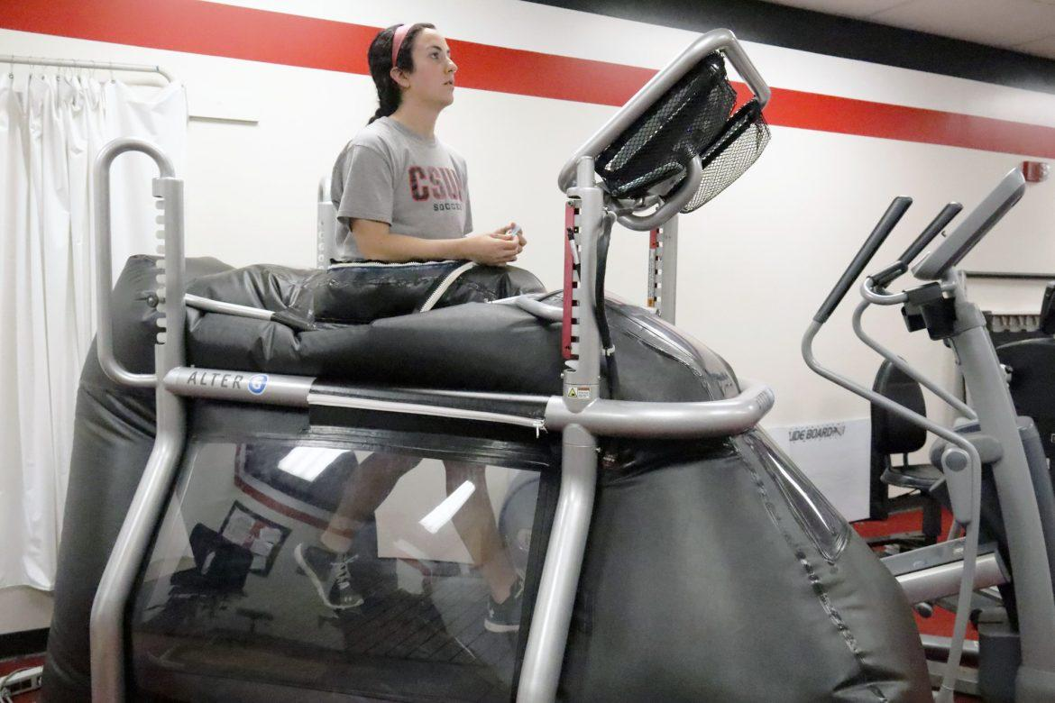 Soccer player Amber Edemann going through a cardio work in an anti-gravitational treadmill that reduces the pressure on her injured knee. Photo credit: Kelcey Henderson