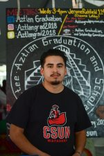 student in red and black CSUN shirt poses in front of Aztlan club poster