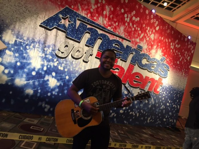 man standing happily in front of Americas Got Talent poster