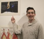 young man happily poses in front of art while pointing towards it