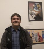 young boy happily poses in front art work on wall