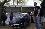 man poses next to black shark painted vehicle
