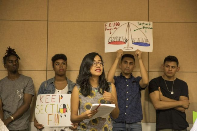 students hold signs of protest to keep section F