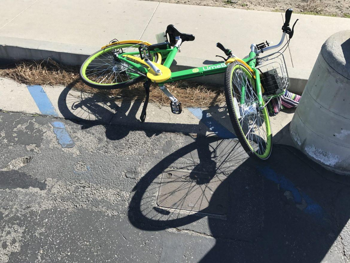 green+and+yellow+limebike+on+the+floor+next+to+the+curb