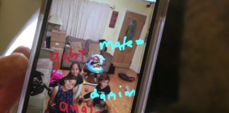 picture of a picture on a phone of 4 young children playing in a living room