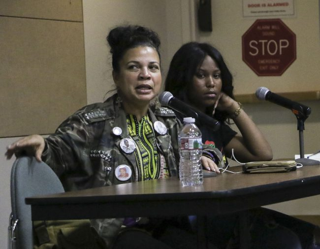 two woman sit at desk speaking into microphone