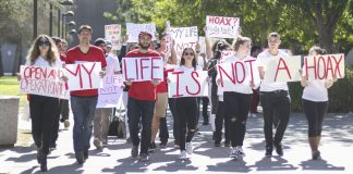 Protesters marching while holding signs reading My Life is Not a Hoax