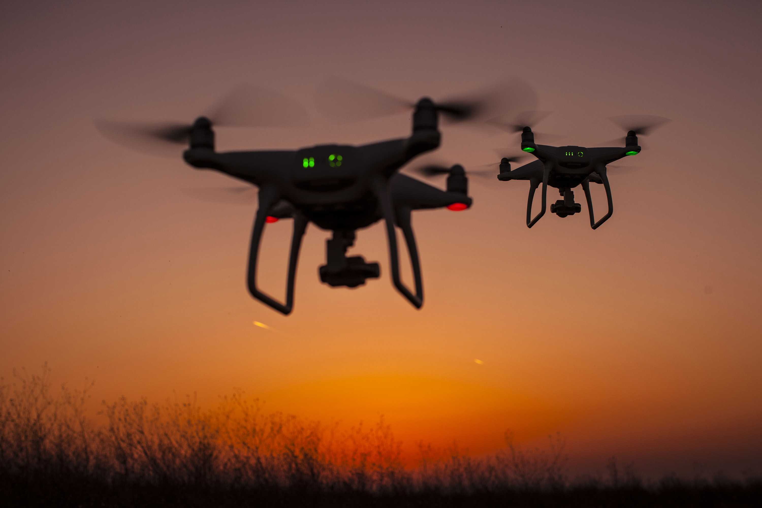 two drones flying in the sunset