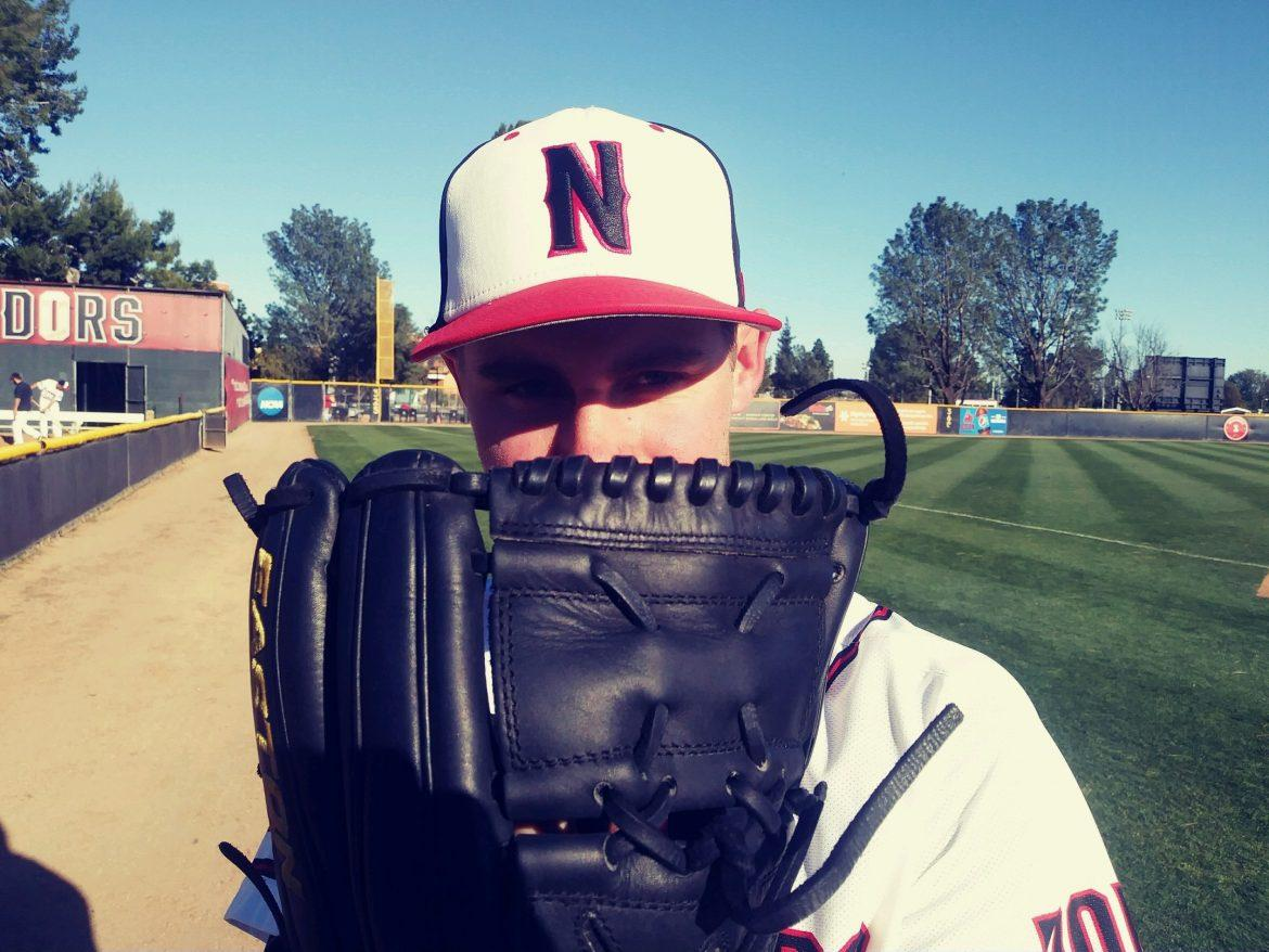 CSUN+baseball+player+in+white+uniform+poses+with+black+baseball+glove+covering+the+bottom+half+of+his+face