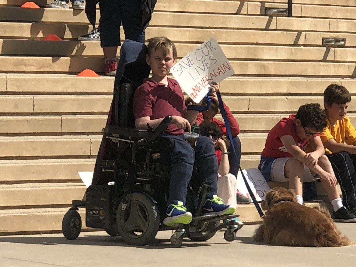 young boy in a wheelchair holds sign reading save our lives Never again