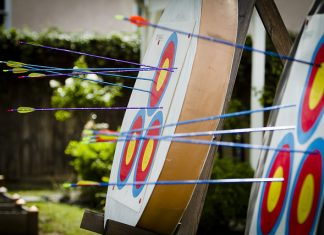 blue and purple archers arrows embedded in red yellow and blue circular targets