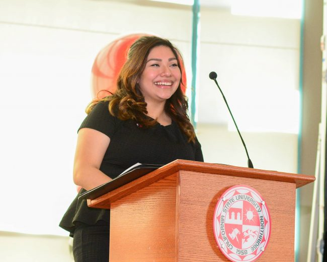 woman happily standing behind a podium dressed in a black blouse