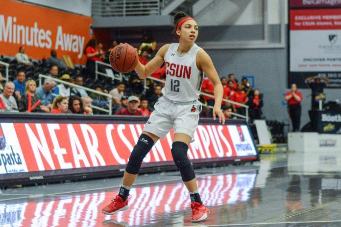 CSUN womans basketball player dribbles ball across the court