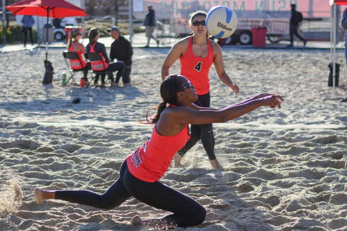CSUN womans beach volleyball players receive the ball in a game