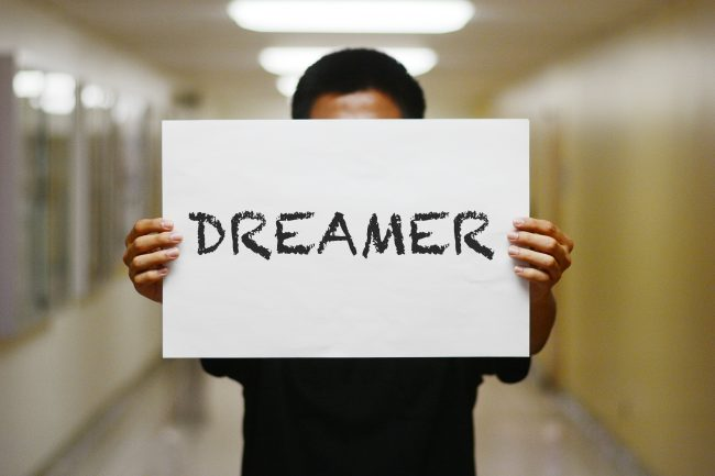 person holds poster reading Dreamer in black lettering