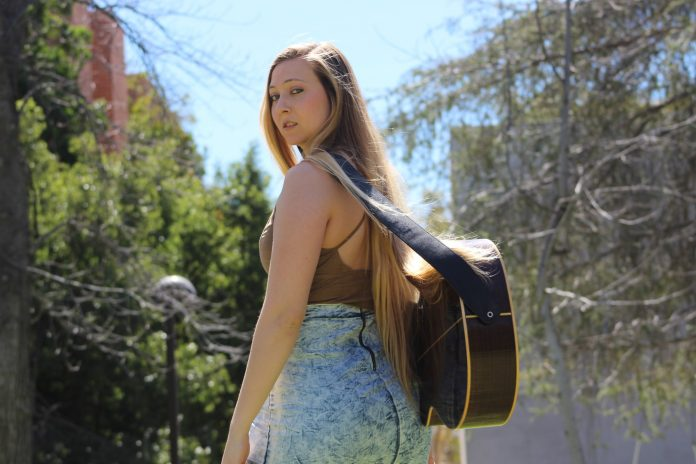 woman with guitar strapped around her back looks seriously into the camera