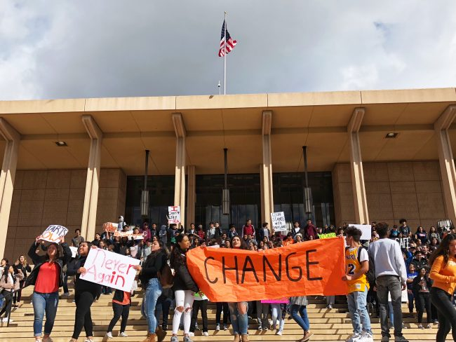 students protest in front of the Oviatt Library holding large signs reading change and never again