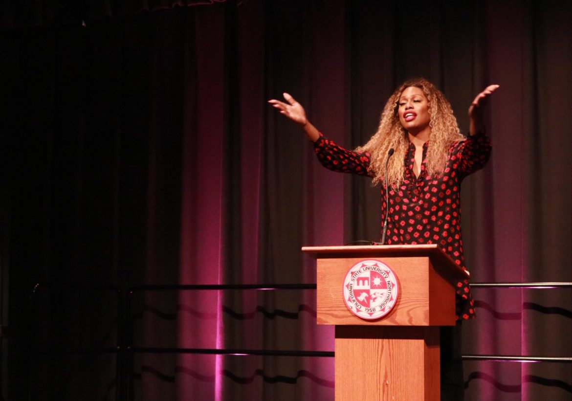 Laverne+Cox+with+her+arms+spread+out+speaking+at+a+podium