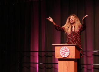 Laverne Cox with her arms spread out speaking at a podium