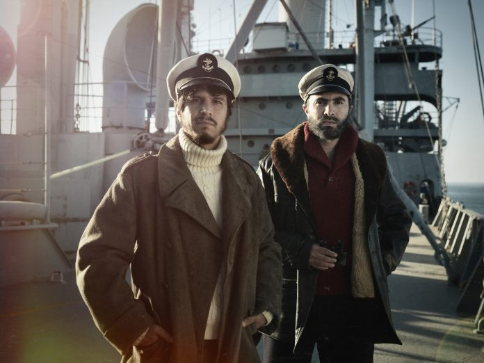 two men dressed warmly standing on the deck of a boat with sailor hats on