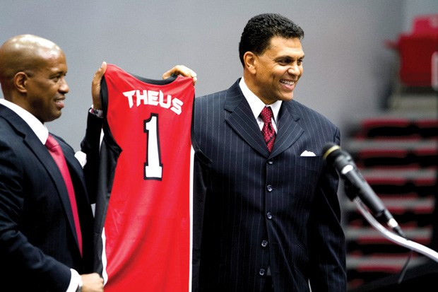 two men professionally dressed hold up red Jersey reading Theus and the number 1